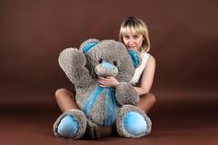 Frau, die einen Teddybären umarmt Stockfotografie