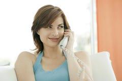 Frau, die einen Telefon-Aufruf und ein Lächeln bildet Stockfoto