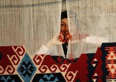 Frau, die einen traditionellen türkischen Teppich spinnt Stockbild