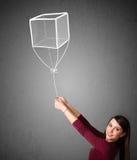 Frau, die einen Würfelballon hält Lizenzfreies Stockbild