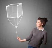 Frau, die einen Würfelballon hält Stockbild