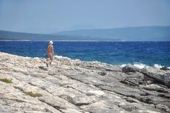 Frau, die einen Weg auf dem Strand in der Badebekleidung hat Stockfotos