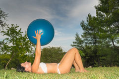 Frau, die einen weißen Badeanzug ausarbeitet trägt, pilates an einem Hausgarten tuend stockfotos