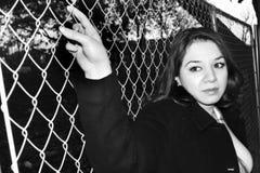 Frau, die einen Zaun anhält Lizenzfreie Stockbilder