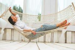 Frau, die in einer entspannenden Hängematte sich entspannt Lizenzfreie Stockfotos