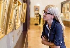 Frau, die in einer Kunstgalerie steht Lizenzfreie Stockfotos