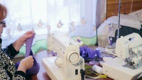 Frau, die an einer Nähmaschine arbeitet Die Frau bereitet das Gewebe für das Nähen vor stock video