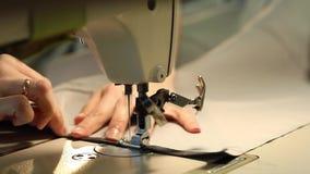 Frau, die an einer Nähmaschine, Nähmaschine der Nadel, weibliche Hände, Zeitlupe-Video, Nahaufnahme, flache Tiefe von arbeitet stock video
