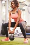 Frau, die in einer Turnhalle mit einem kettlebell Gewicht, vertikal trainiert Lizenzfreie Stockfotos