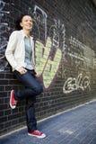 Frau, die an einer Wand sich lehnt Stockfotografie