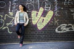 Frau, die an einer Wand sich lehnt Lizenzfreie Stockbilder