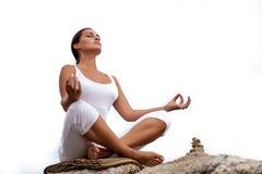 Frau, die in einer Yogahaltung auf dem Strand meditiert Stockbilder