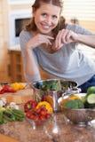 Frau, die einige Gewürze ihrer Mahlzeit hinzufügt Stockbild