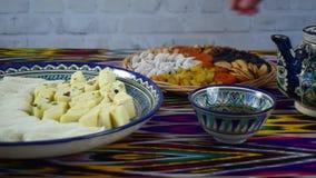 Frau, die einige orientalische Bonbons von der Tabelle im Café, Samarkand, Usbekistan nimmt stock video