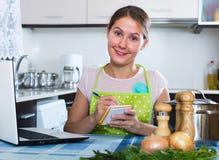 Frau, die Einkaufsliste an der Küche macht Stockbild
