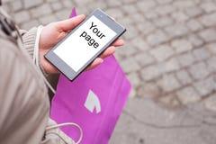Frau, die Einkaufstasche und Handy hält. Stockfotografie