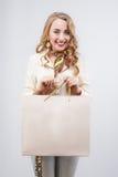 Frau, die Einkaufstaschen gegen einen weißen Hintergrund hält Stockbilder