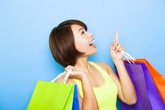 Frau, die Einkaufstaschen hält und oben schaut Lizenzfreie Stockfotos
