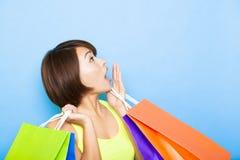 Frau, die Einkaufstaschen hält und oben schaut Stockbilder