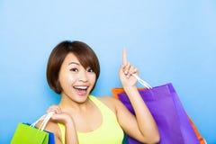 Frau, die Einkaufstaschen hält und oben zeigt Lizenzfreie Stockfotos