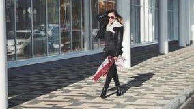 Frau, die Einkaufstaschen, Kamera und das Lächeln betrachtend hält stock footage