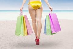 Frau, die Einkaufstaschen am Strand hält Stockfoto
