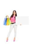 Frau, die Einkaufstaschen und eine leere Fahne hält Stockfotografie