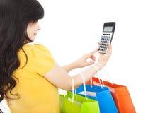 Frau, die Einkaufstaschen und -taschenrechner anhält lizenzfreies stockbild