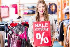 Frau, die Einkaufsverkaufsfahne zeigt lizenzfreie stockbilder