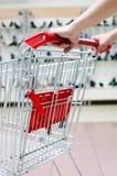 Frau, die Einkaufswagen drückt Stockfotografie