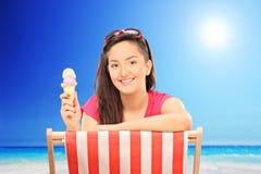Frau, die Eiscreme am sonnigen Tag durch den Strand isst Stockfotografie