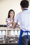 Frau, die Eiscreme vom Kellner At Counter empfängt Lizenzfreie Stockfotos