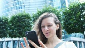 Frau, die emotional das Telefon - Überraschung auf dem Hintergrund von Wolkenkratzern untersucht stock video
