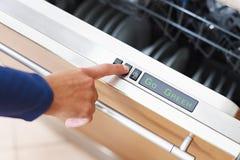 Frau, die Energiesparertaste auf Spülmaschine bedrängt Lizenzfreie Stockbilder