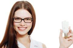 Frau, die Energiesparlampe hält Stockbild