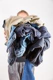 Frau, die enormen Stapel der schmutzigen Kleidung hält stockbilder
