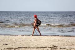 Frau, die entlang das Meer geht Lizenzfreie Stockfotografie