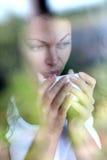 Frau, die entlang des Fensters anstarrt Lizenzfreie Stockfotografie