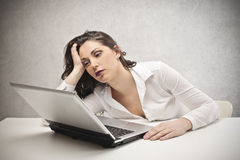 Frau, die entlang des Laptops anstarrt Stockfoto