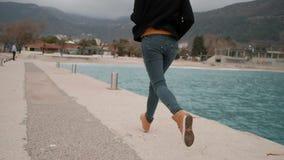 Frau, die entlang Pier, Damm nahe See läuft Ansicht von der Rückseite stock video footage