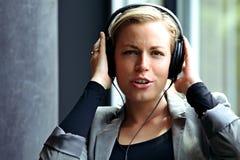 Frau, die entlang zur Musik auf Kopfhörern singt Lizenzfreies Stockfoto