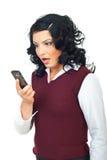 Frau, die entsetzt schaut, um Mobile anzurufen Stockfotos