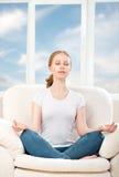 Frau, die, Entspannung, sitzend in einem Lotussitz auf meditiert lizenzfreie stockbilder