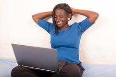 Frau, die Entspannungsauf dem Bett zu Hause sitzen des Laptops verwendet lizenzfreie stockfotografie