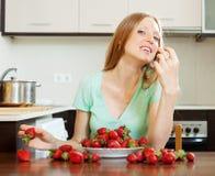 Frau, die Erdbeere in der Hauptküche isst Lizenzfreies Stockbild