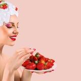 Frau, die Erdbeere isst Stockfoto