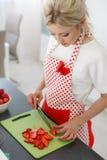 Frau, die Erdbeeren auf Küchentisch schneidet Stockfoto