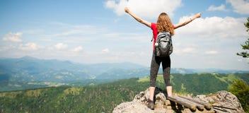 Frau, die Erfolg mit den Armen gestikuliert, oben nachdem dem Klettern zur Spitze stockfotografie