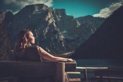 Frau, die erstaunliche Ansicht von Lago di Braies mit Gebirgswald auf dem Hintergrund genießt Lizenzfreie Stockbilder