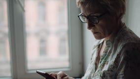 Frau, die etwas auf dem Smartphoneschirm aufpasst stock footage